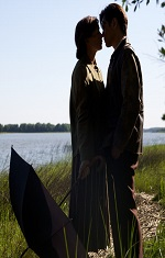 A man and a woman in period clothes embrace near a river.