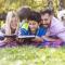 una familia y su perrito leen un libro en un parque