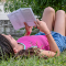 Young girl reading a novel on lush green grass