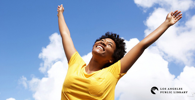 women in yellow t-shirt with her arms raised high against a blue sky