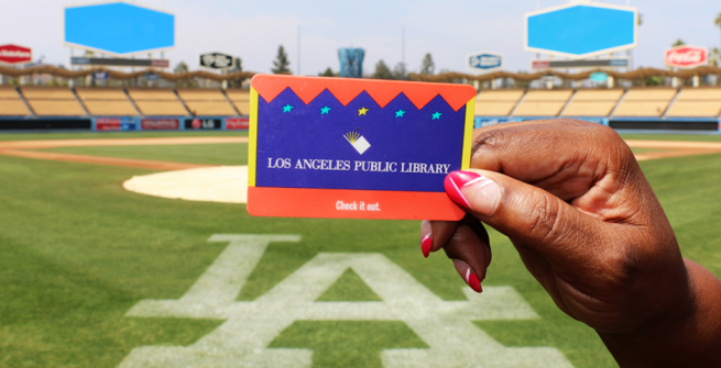 African-American woman holding up a Los Angeles Public Library card. Only her hand and card are visible. It's a bright sunny day at Dodger stadium where this photograph took place.