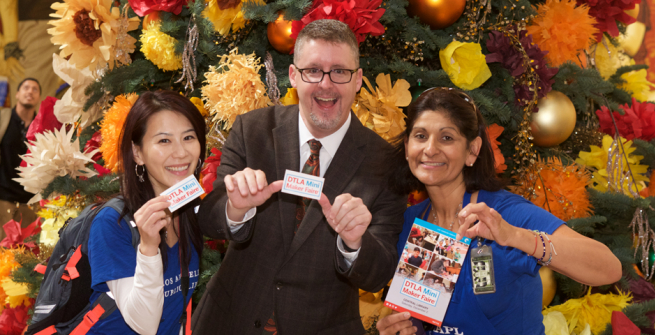 3 librarians holding library cards in front of a holiday tree
