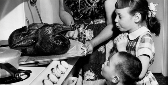children oohing at turkey coming out of the oven