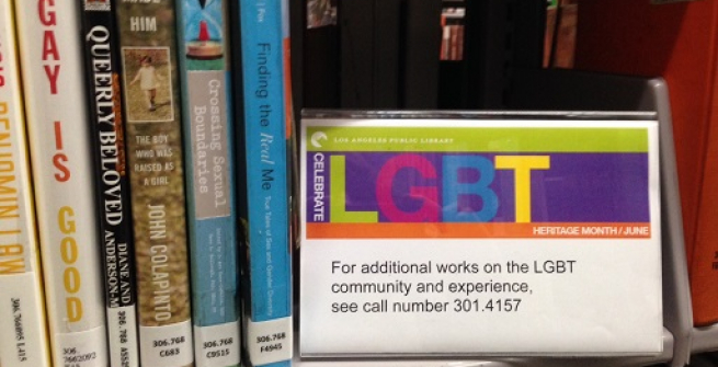 stack of books with lgbt sign