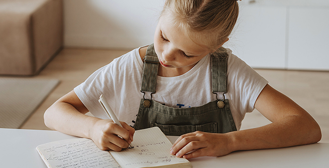 Young girl writing in her journal