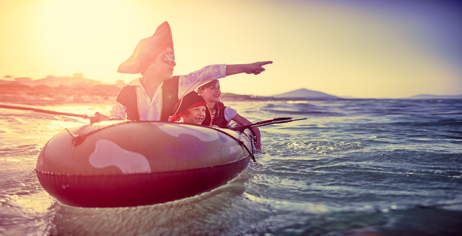 Kids dress in pirate clothes enjoying seafaring adventures while floating in a dinghy