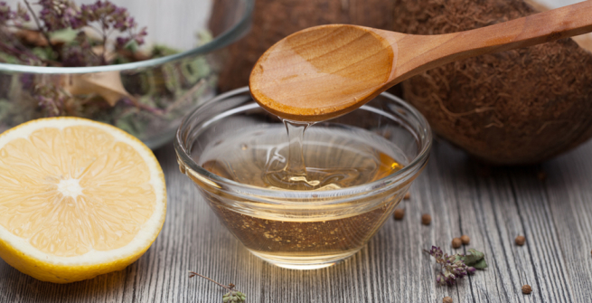 wooden spoon and bowl of honey next to a lemon
