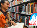 James Paul Ancheta holding a book in the library stacks with DTLA Mini Maker Faire Logo