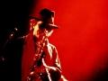 Gato Barbieri en concierto toca su saxofón bajo luces rojas en el escenario