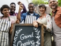 Group of ethnic twenty somethings with a grand opening sign
