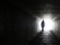 a person walking to the light at the end of a tunnel