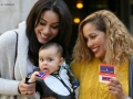 two ladies holding a baby chewing on a library card