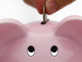 A coin being inserted in a piggy bank