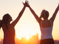 Two women celebrating with arms raised as they look at sunrise
