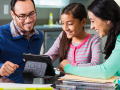 hispanic mom and dad use digital tablet to help with homeschool assignment for their pre-teen female student.