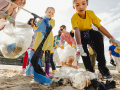 Kids and parents clean up trash from a beach