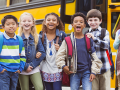 Happy, laughing diverse tweens standing near a school bus