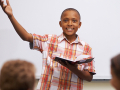 Young person speaking with enthusiasm in front of his classroom
