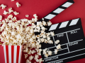 popcorn and film clapper on a red background
