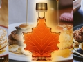 A maple-shaped bottle in front of food items using maple syrup.