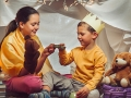 Happy girl and boy playing at home in a homemade tent