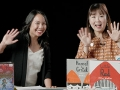 two women waving from behind a display of children's books