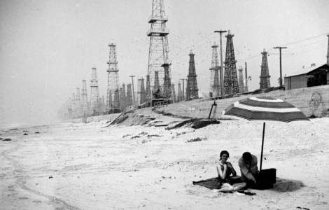 A couple spread out a picnic in the shadows of Huntington Beach oil derricks, circa 1937