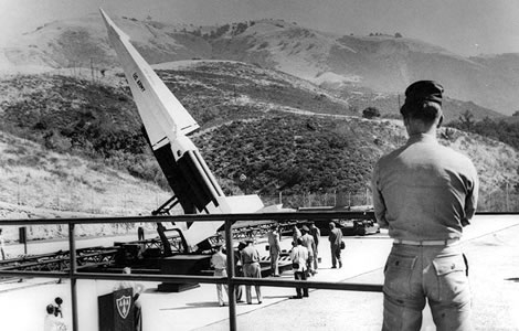 Soldier stands guard over poised Nike guided missile. Four Nike bases form main line of defense for critical Valley area. Sep. 8, 1960.