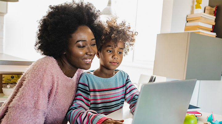 mother and child sitting in front a laptop