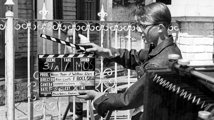 1950s teen holding a movie clapboard