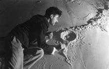 Man with plaster scale model of moon