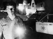 Sheriff's Deputy Bill Phelton with light at night in front of police car