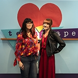 2 women in front of the teenscape sign