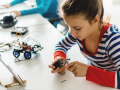 Young girl building an electronic device