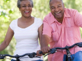 Two senior citizens, man and women, are riding bicycles, laughing and smiling