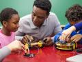 adult and kids working on robotics