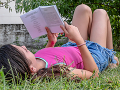 young person reading a book on the grass